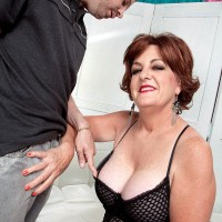 Busty MILF over 60 Gabriella LaMay giving a blowjob to fat cock in mesh dress