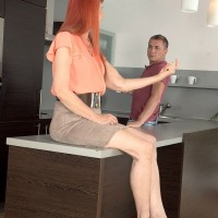 Redheaded MILF over 60 showing off great legs underneath skirt in kitchen