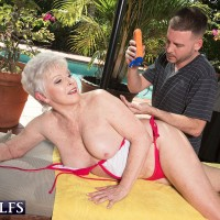 Short haired granny letting big boobs free from bikini outdoors beside pool