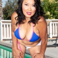Sixty plus oriental MILF Mandy Thai strips off a bathing suit to get buck naked out by a pool