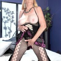 Fair-haired grandmother Charlie uncovers her monster-sized tits in over the knee boots and a fishnet bodystocking