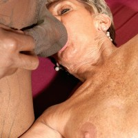 Bosomy stocking and lingerie attired Seventy plus granny Sandra Ann providing gigantic black penis a blow job