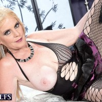 Golden-haired granny Charlie exposes her massive melons in over the knee boots and fishnet body-stocking