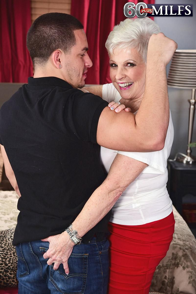 MILF Over 60 Jewel seduces a younger boy in a tight red skirt in her bedroom