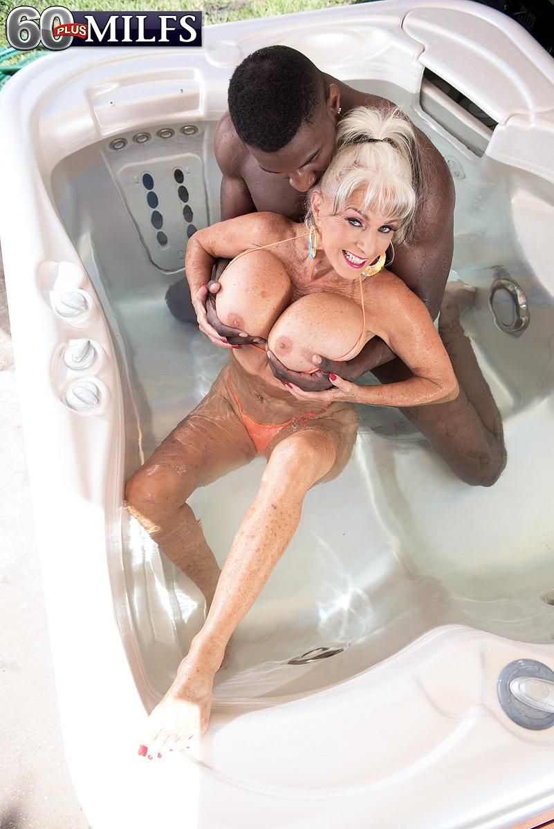 Busty MILF over 60 Sally D'Angelo plays with a big black dick in a hot tub