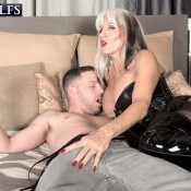 Hot MILF over 60 Sally D'Angelo dominates a boy in a corset and thigh high boots