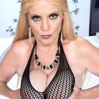 Over 60 yellow-haired MILF whipping out hefty natural breasts in ripped tights and long boots