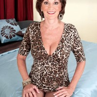 Solo granny Sydni Lane teasing on bed by displaying brassiere in pantyhose