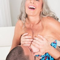 Super-sexy 60 plus MILF Silva Foxx entices a younger dude by showing off her hooters in a denim microskirt